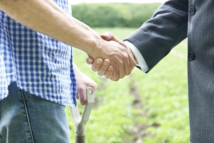 畑で握手する男性